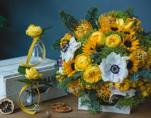 White yellow flower bouquet and small flask vases around Free Photo