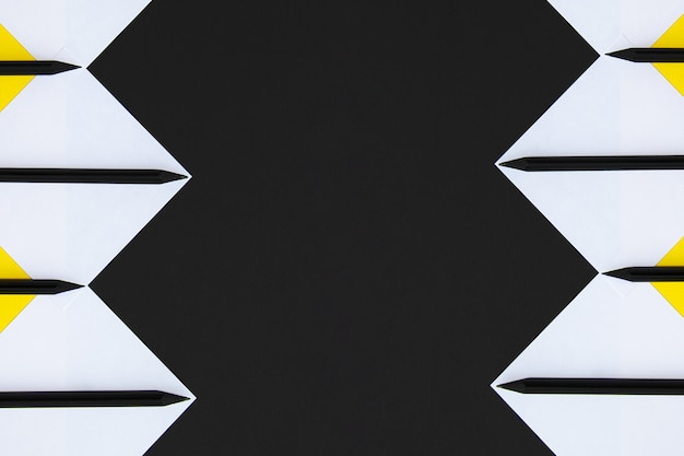White and yellow stickers with black pencils lined with a geometric pattern on a black background. Premium Photo