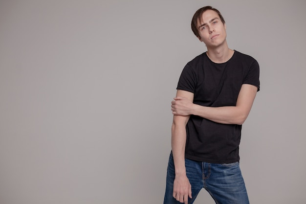 White young man in a black t-shirt and jeans. emotion. Premium Photo