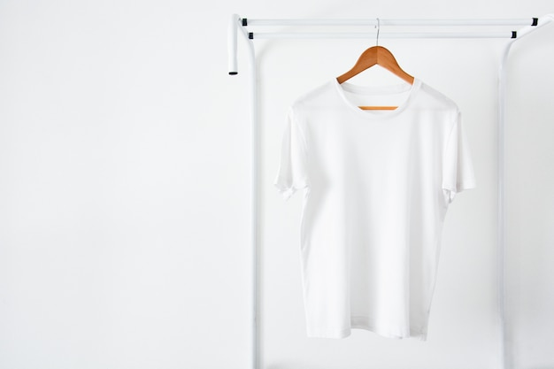 Whitet-shirt hanging on wooden hanger Premium Photo
