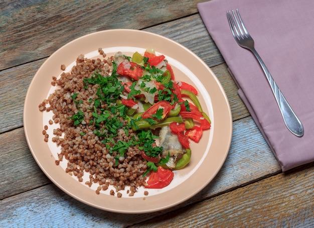 野菜、トマト、ピーマン、タマネギと焼いた魚の青いwhitingの飾りとそば米雑炊 Premium写真