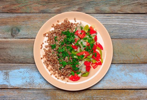 野菜、トマト、ピーマン、玉ねぎ、木製の背景、上面のクローズアップで焼いた魚の青いwhitingの飾りとそば米雑炊 Premium写真