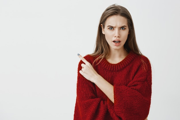 Who invited that drunk guy to party. studio shot of displeased angry young woman in red loose sweater, frowning and arguing with friend, pointing at upper left corner Free Photo