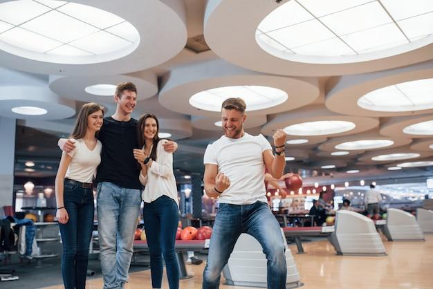Chi è il vincitore. i giovani amici allegri si divertono al bowling durante i fine settimana Foto Gratuite