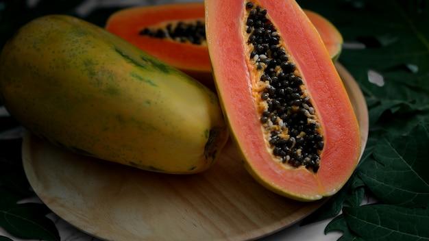 Целая и наполовину сладкая папайя на деревянной тарелке Premium Фотографии