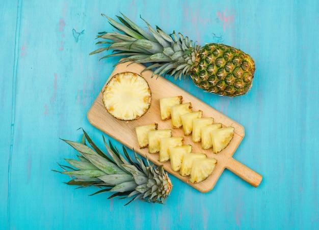 ブルーシアンのまな板の上から見ると全体とスライスしたパイナップル 無料写真