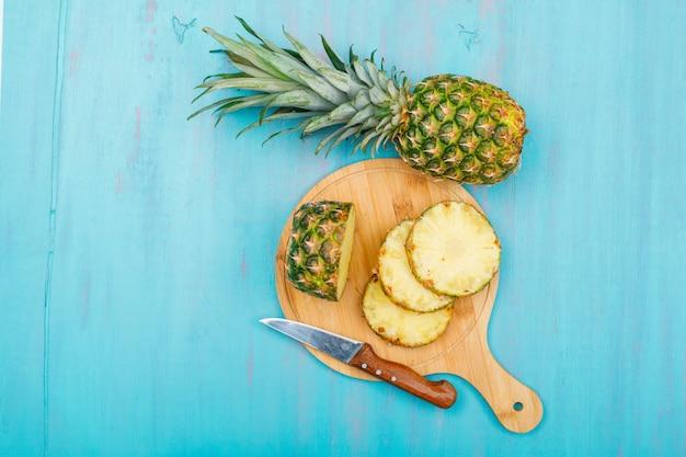 ブルーシアンのフルーツナイフ上面とまな板で全体とスライスしたパイナップル 無料写真