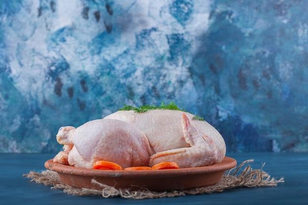 파란색 표면에 삼베 냅킨에 접시에 전체 닭고기와 얇게 썬 당근 무료 사진