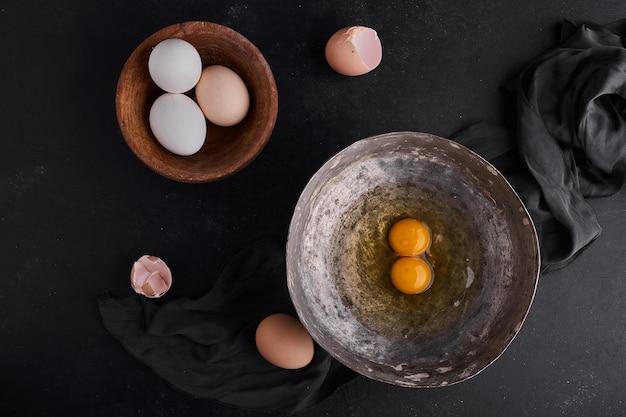 木製および金属板の全卵と卵黄、上面図。 無料写真
