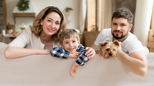 Вся семья с собакой, сидя на диване Бесплатные Фотографии