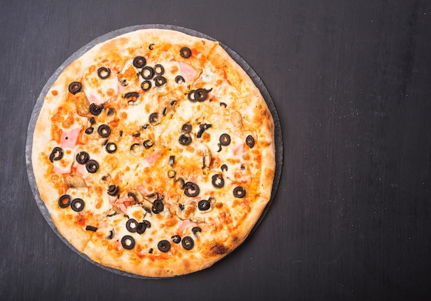 Whole fresh pizza with olives and meat topping on slate over dark backdrop Free Photo