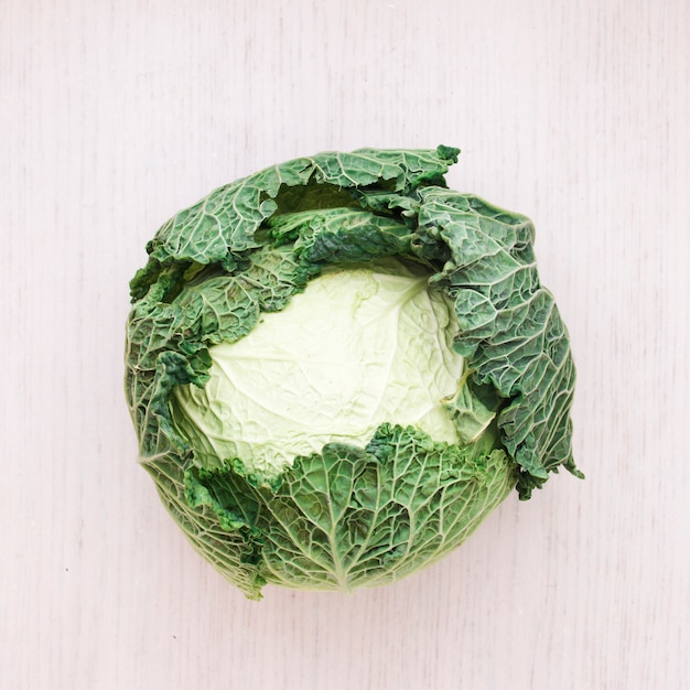 Whole fresh savoy cabbage on wooden surface Free Photo