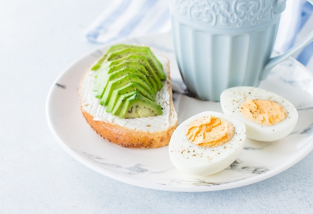 Whole grain bread sandwiches with avocado and boiled eggs on wooden board and coffee Premium Photo