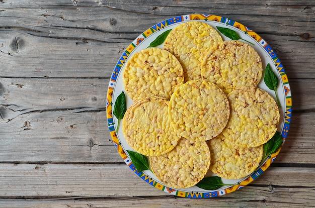 Хрустящие хлебцы всего зерна с шпинатом выходят на плиту на старый деревянный стол. здоровая концепция завтрака или диеты. Premium Фотографии