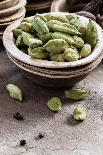 Whole green cardamom in a bowl on wood Premium Photo