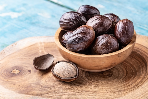 Whole nutmeg nuts in a bowl on blue rustic wooden table. Premium Photo