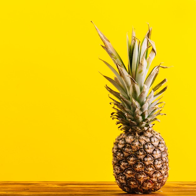 Whole pineapple on table against yellow background Free Photo