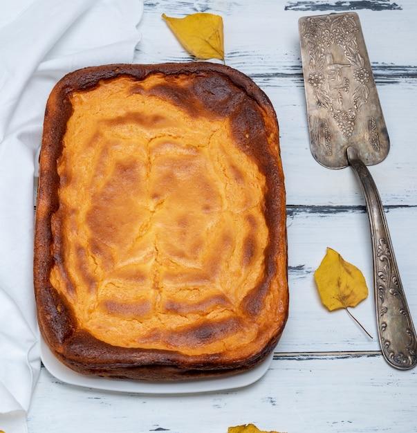 Whole rectangular pie of cottage cheese and pumpkin Premium Photo