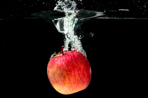 Whole red apple falling in water over black background Free Photo