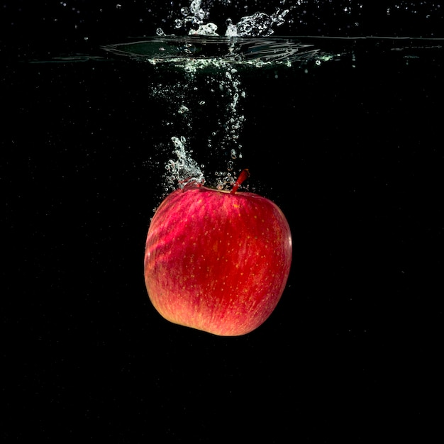 Whole red apple splashing in water against black background Free Photo