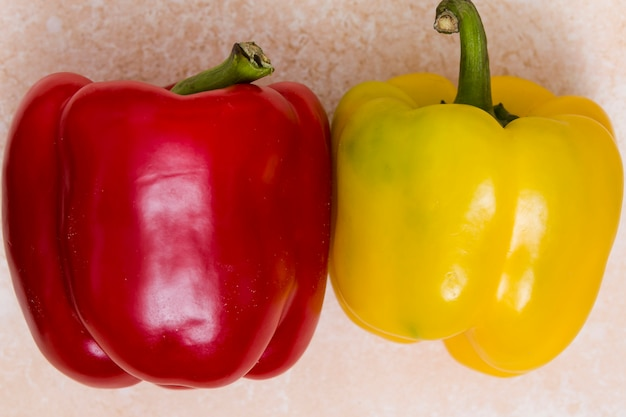 Whole red and yellow bell peppers on textured backdrop Free Photo