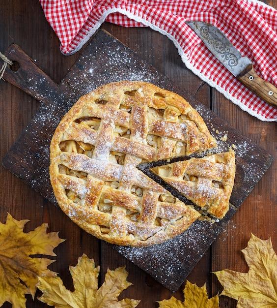 Whole round apple pie on a rectangular old brown board Premium Photo