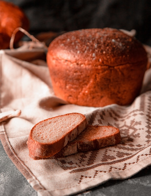Whole round bread with thin slices on a white tablecloth Free Photo