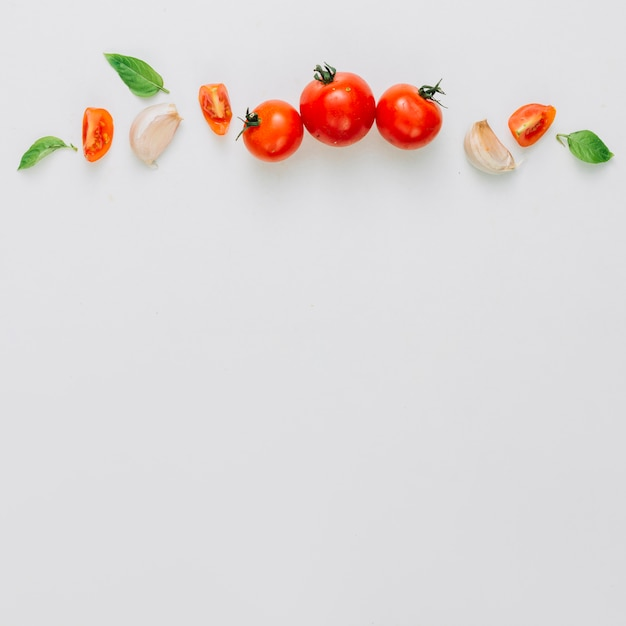 Whole and slice of cherry tomatoes; garlic clove and basil over the white background Free Photo