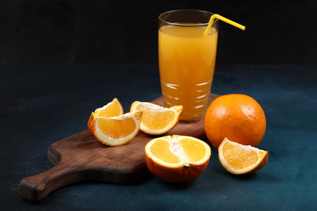 Whole and sliced oranges with a glass of juice. Free Photo