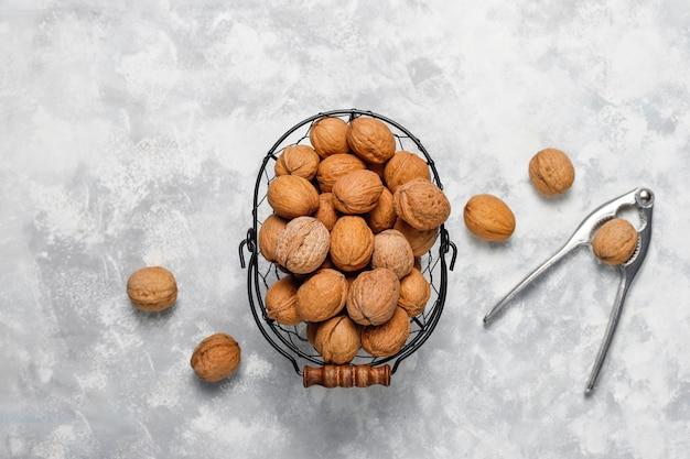 Whole walnuts in shell in food metal basket, walnut kernels. top view on concrete Free Photo