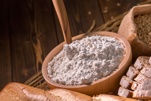Whole wheat bread, flour blow and oat on wood table. Premium Photo
