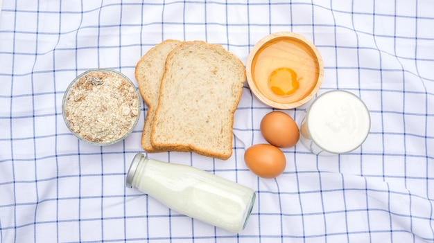 Whole wheat bread, oat, chicken egg, yogurt and milk on a table. Premium Photo