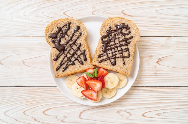 Whole wheat bread with fresh banana, strawberry and chocolate Premium Photo