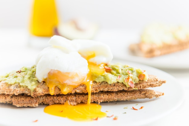Wholemeal bread toast and poached egg with mashed avocado and ch Premium Photo