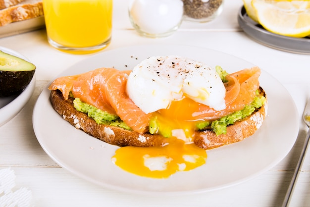 Wholemeal bread toast, smashed avocado, salmon and poached egg Premium Photo