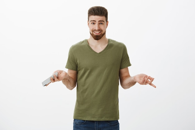 Why not order food online. easygoing questioned attractive bearded man in t-shirt shrugging with hands sideways holding smartphone, unbothered, having no big deal with picking presents in internet Free Photo