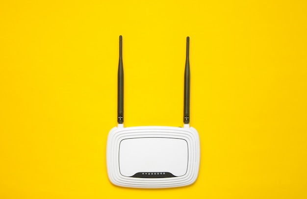 Wi-fi router on a yellow background. trend of minimalism. always online. top view. Premium Photo