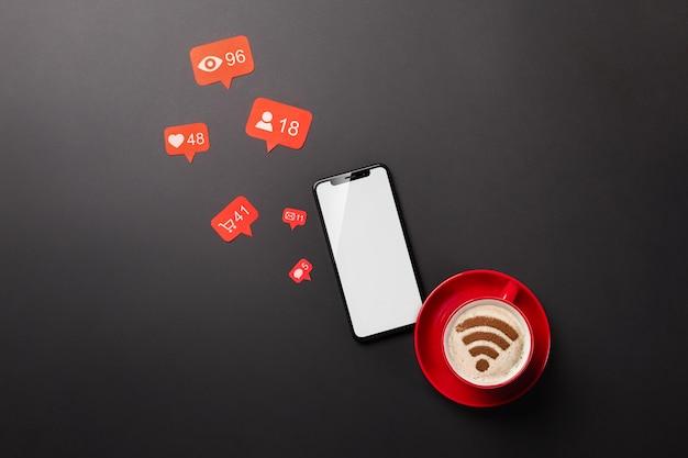 一杯のコーヒー、電話、wi-fiサインが入った黒いデスクトップ上のラップトップは、ソーシャルネットワークで機能します。上面図 Premium写真