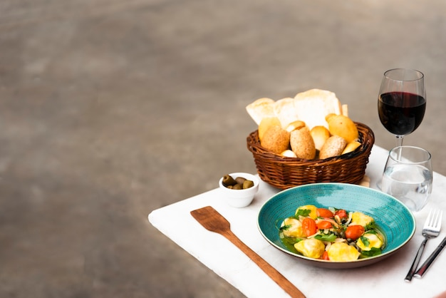 Wicker basket of bread and cooked ravioli pasta on white table Free Photo