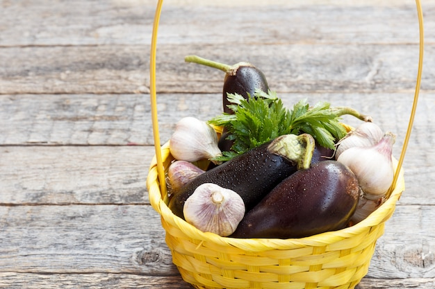 A wicker basket of vegetables eggplant garlic greens on wooden concrete background on the street. Premium Photo