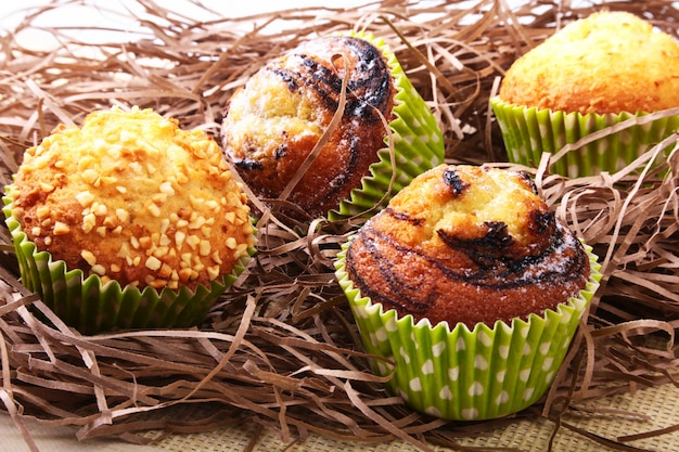 Wicker basket with assorted delicious homemade muffins with raisins and chocolate. Premium Photo