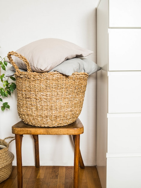 Wicker basket with  gray cushions  on a wooden vintage chair  against  white wall Premium Photo