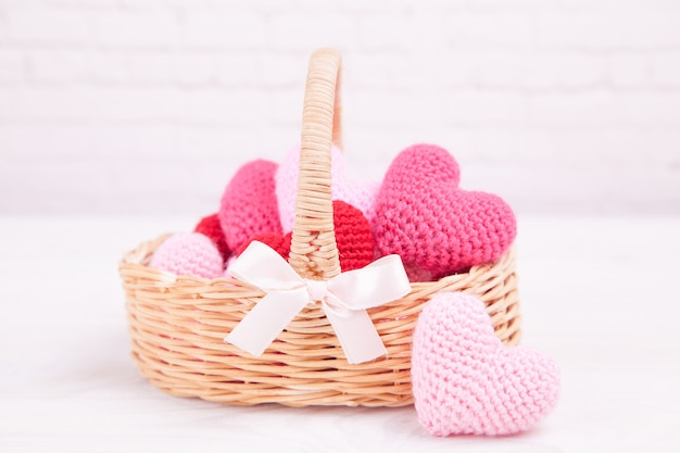 Wicker basket with multi-colored knitted hearts. festive decor. valentine's day Premium Photo