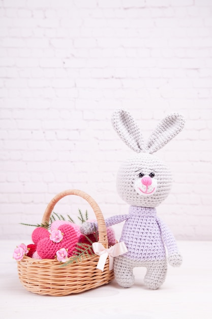 Wicker basket with multi-colored knitted hearts. knitted rabbit. festive decor. valentine's day. handmade, knitted toy, amigurumi Premium Photo