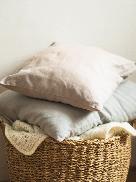 Wicker basket with a white soft knitted blanket and gray cushions against a white wall Premium Photo