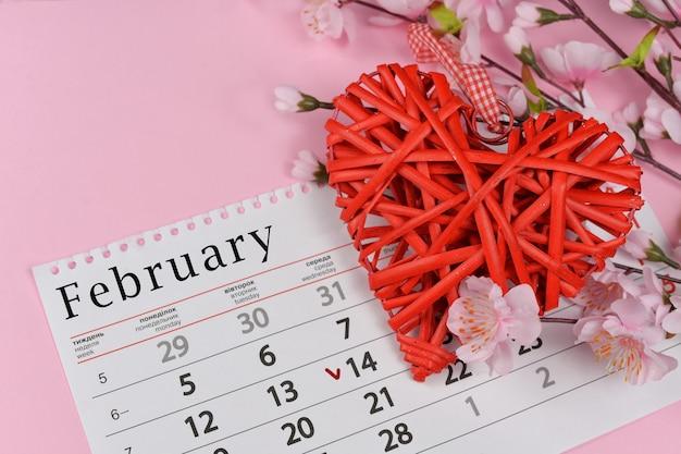 カレンダーとピンクの花と籐の赤いハート Premium写真
