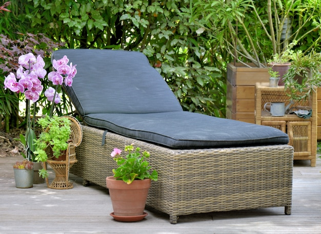 Wicker sunbath in wooden terrace for relaxing in  home garden Premium Photo