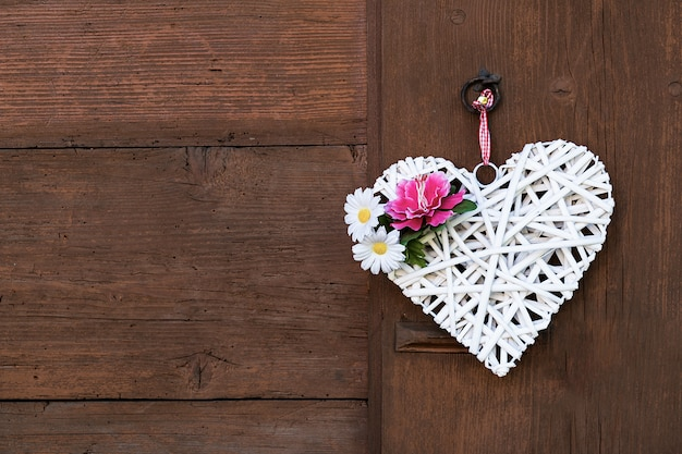 Wicker white heart with peony and daisies hanging on a wooden wall. Premium Photo