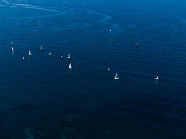 Широкий воздушный снимок маленьких белых парусников, плавающих в океане близко друг к другу Бесплатные Фотографии
