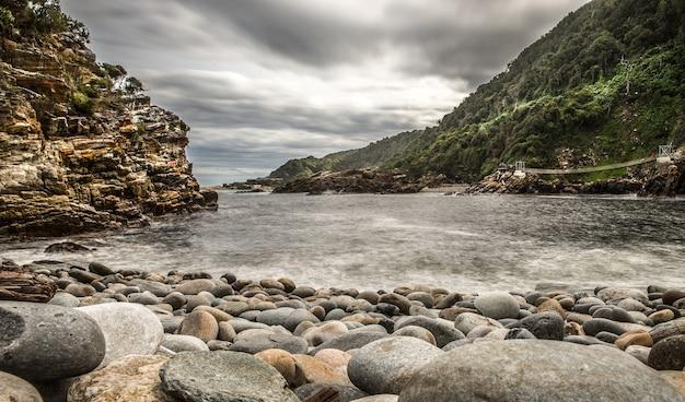 Colpo grandangolare della spiaggia intorno alle montagne sotto un cielo nuvoloso Foto Gratuite